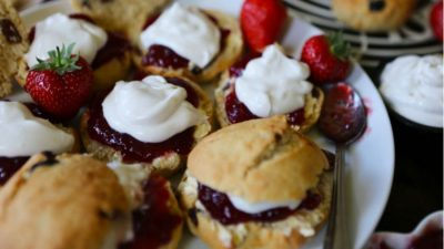 A plate of scones with cream and jam.