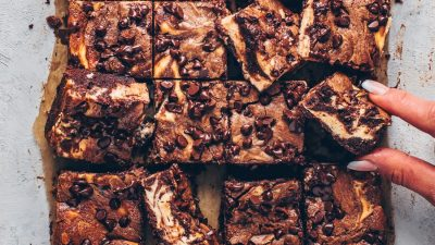 A tray of brownies with cheesecake marbled through.
