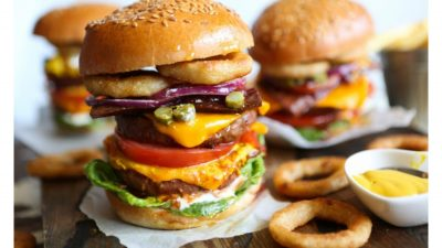 A huge burger with onion rings on the side.
