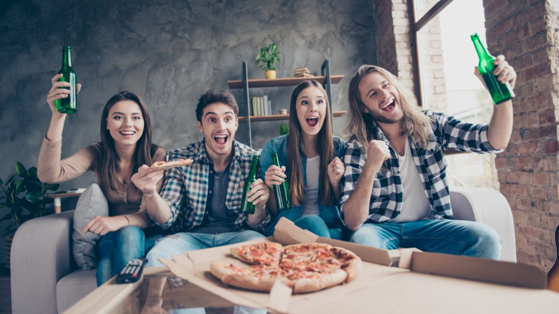 A group of friends share a pizza and beer together.