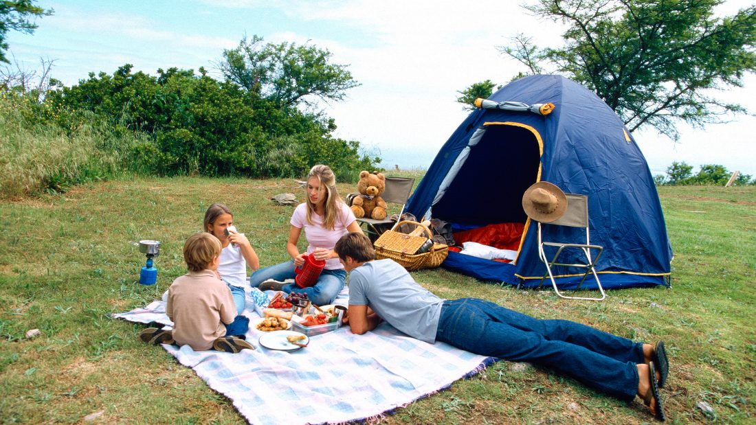 A family enjoying food on a camping trip.